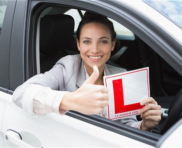 Young female driving lesson student with thumbs up sat in car holding a learner plate