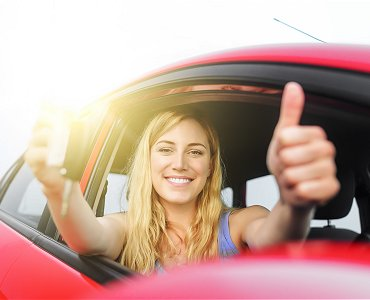 Young female driving lesson student sat in car with thumbs up